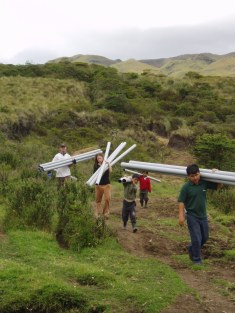 Helping move pipes for water, Ecuador, 2004